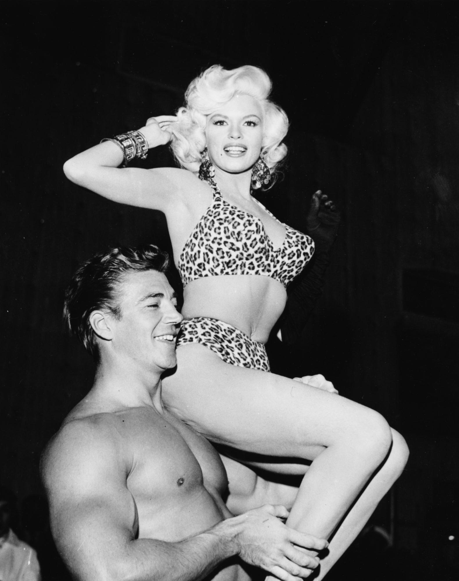 Jayne Mansfield de biquíni com padrão leopardo, ao colo do marido Mickey Hargitay, em 1956.
